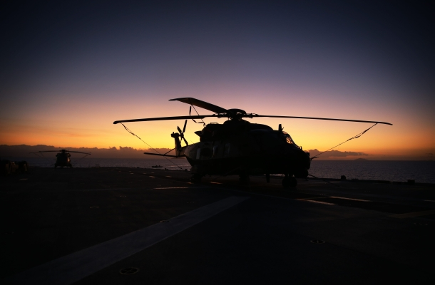 A MRH-90 helicopter from 5th Aviation Regiment on the flight deck of HMAS Canberra at sunset during Sea Series 2015.