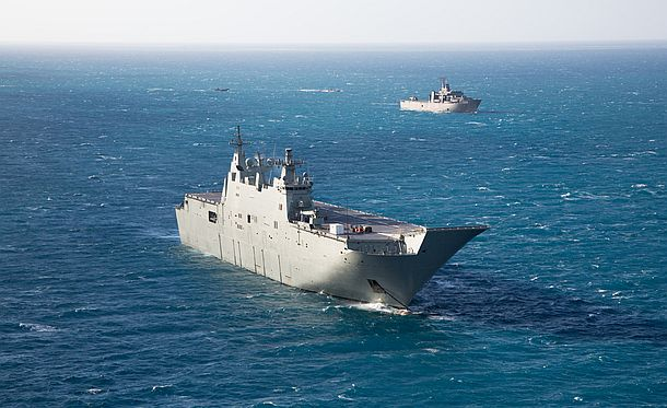 HMAS Adelaide and Republic of Singapore Ship Resolution at anchor off the coast of North Queensland, as RAN helicopters and landing craft from both navies conduct cross deck training between the two amphibious platforms. Credit: Defence