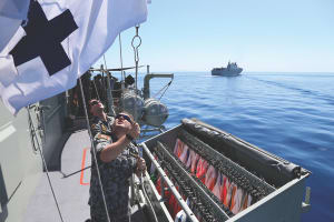 Signalmen on HMAS Stuart communicate via flag during Officer of the watch manouevres with HMAS Canberra. Credit: Defence