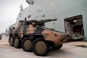 A Rheinmetall Boxer combat reconnaissance vehicle drives onto the heavy vehicle deck of the Royal Australian Navy amphibious ship HMAS Canberra during a series of trials at Fleet Base East in Sydney on 6 December 2016. Credit: Defence