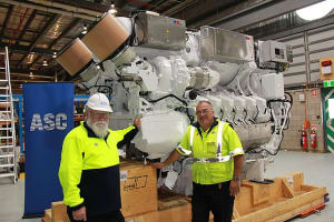 ASC picture of an MTU submarine engine to be tested, with two of ASC's Adelaide staff. Credit: ASC