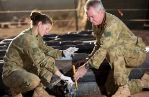 Australian Army soldiers Sergeant Ian Myles (right) and Corporal Alyce Humrich from 1st Preventative Medicine Company, 2nd General Health Battalion, collect a water sample from Camp Birt water storage facility in Titjikala, Northern Territory, in July 2015. Credit: Defence