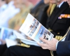 A guest at the launch of The 2013 Defence White Paper has a quick read. [Photo:Defence]