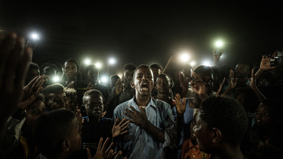 WINNER: WORLD PRESS PHOTO OF THE YEAR . © Yasuyoshi Chiba, Agence France-Presse. A young man, illuminated by mobile phones, recites a poem while protestors chant slogans calling for civilian rule, during a blackout in Khartoum, Sudan, on 19 June.