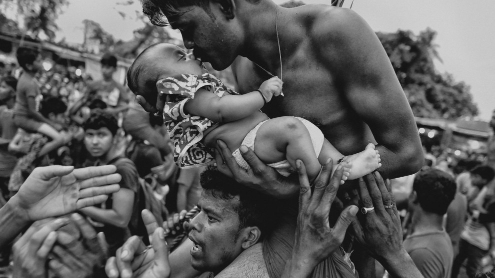 3rd Place in People. Photograph and caption by Avishek Das / 2018 National Geographic Photo Contest. A Hindu devotee kisses his newborn baby during the Charak Puja festival in West Bengal, India. Traditional practice calls for the devotee to be pierced with a hook and sometimes swung from a rope. This painful sacrifice is enacted to save their children from anxiety. While covering the festival, I was able to view the religious practice from the perspective of Hindu devotees. I tried to capture the moment of love and bonding between a father and his child—and show a father's concern for his little son.