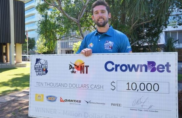 Ex-Hawthorn AFL player Brent Renouf with the cheque for $10k after catching one of last year's tagged barra.