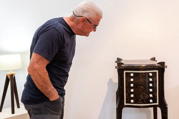 A visitor admires the Collector's Cabinet made by Ian Higgs. Warwick Wright's Apollo lamp is to the left. Photo: Julijana Griffiths