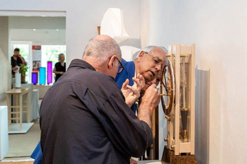 David Boucher takes a closer look at Will Matthysen's clock with the maker on hand to answer questions. Photo: Julijana Griffiths