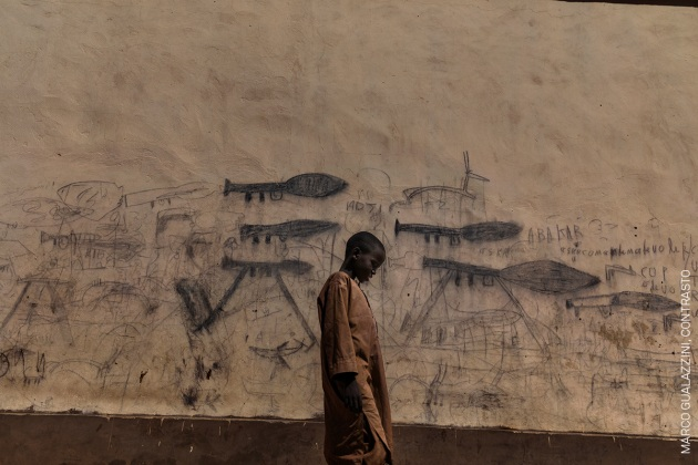 Almajiri Boy. An orphaned boy walks past a wall with drawings depicting rocket-propelled grenade launchers, in Bol, Chad. © Marco Gualazzini, Contrasto