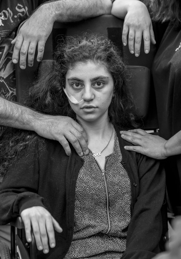 World Press Photo of the Year Nominee. © Tomek Kaczor, Poland, for Duży Format, Gazeta Wyborcza. Awakening. A 15-year-old Armenian girl who has recently woken from catatonic state brought on by Resignation Syndrome, sits in a wheelchair, flanked by her parents, in a refugee reception center in Podkowa Leśna, Poland.