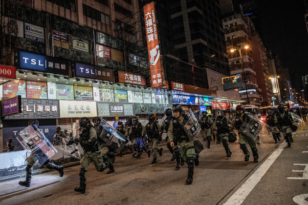 Nominee for the World Press Photo Story of the Year. © Nicolas Asfouri, Denmark, Agence France-Presse. Hong Kong Unrest. Riot police run towards protesters on Nathan Road in Hong Kong, on 1 December 2019.