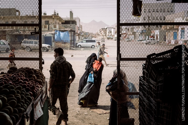 A woman begs outside a grocery store in Azzan, a pivotal southern crossroads town that had seesawed back and forth between government and insurgent forces, on 22 May. Yemen Crisis. © Lorenzo Tugnoli, Contrasto, for The Washington Post.