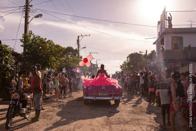 The Cubanitas. Pura rides around her neighborhood in a pink 1950s convertible, as the community gathers to celebrate her fifteenth birthday, in Havana, Cuba. © Diana Markosian, Magnum Photos