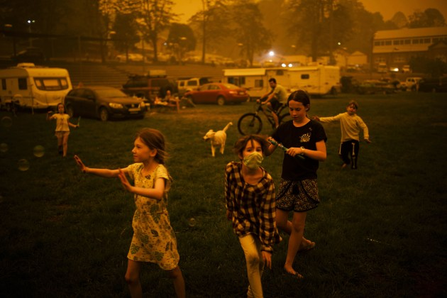 © Sean Davey, Australia, for Agence France-Presse. Bushfire Evacuation Center. Abigail Ferris (in mask) plays with friends at a temporary evacuation center in Bega, New South Wales, Australia, on 31 December. Abigail and her family had been evacuated from a nearby camping spot during bushfires on New Year's Eve.