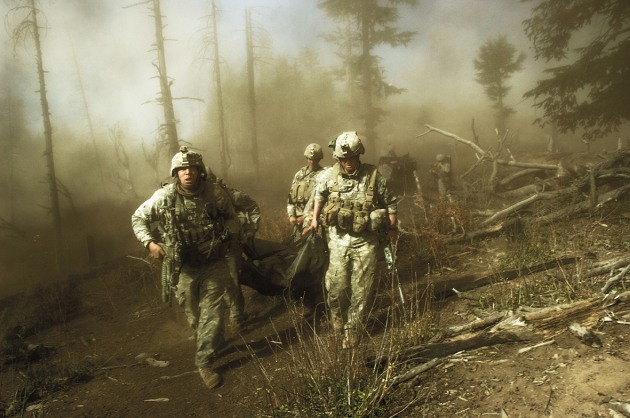 © Lynsey Addario. U.S. troops with the 173rd Airborne, Battle Company, carry the body of Staff Sgt. Larry Rougle after he was killed in an ambush during Operation Rock Avalanche in the Korengal Valley, October 2007.