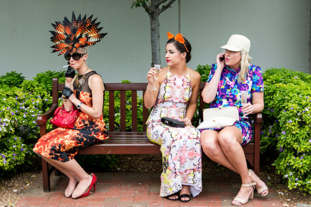 © Asanka Brendon Ratnayake. A women with a colourful headpiece sitting on a bench smokes a cigarette during the Emirates Melbourne Cup Day, held at Flemington Racecourse in Melbourne Australia.