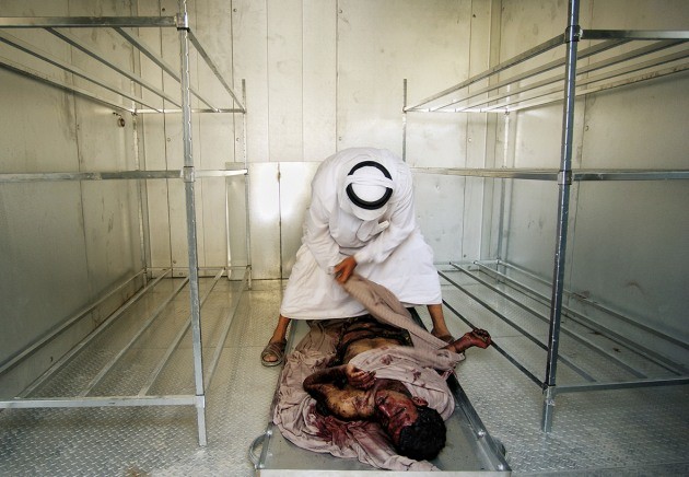 © Lynsey Addario. Abdul Munim Ali Hamood wraps the body of his only son in the Al Karama morgue after he was killed in a car bomb attack in Baghdad, Iraq, June 2004.
