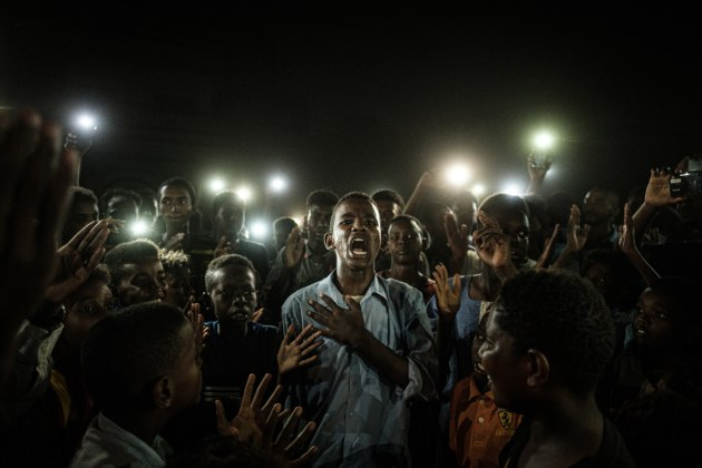 General News Singles Nominee. © Yasuyoshi Chiba, Japan, Agence France-Presse. Straight Voice. A young man, illuminated by mobile phones, recites a poem while protestors chant slogans calling for civilian rule, during a blackout in Khartoum, Sudan, on 19 June.