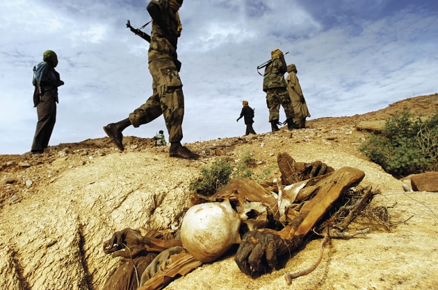 © Lynsey Addario. Sudanese People's Liberation Army soldiers walk past a skeleton left from an attack on civilians in the district of Farawiya, in northwest Darfur, August, 2004.