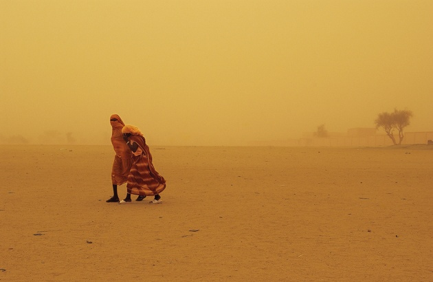 © Lynsey Addario. Two women walk through  a sandstorm in Bahai, Chad, along the border with Darfur, Sudan, August, 2004.