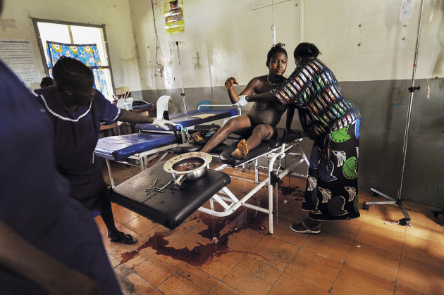© Lynsey Addario. Blood continues to leak from Mamma Sesay (18) shortly after she delivered the second of twins, as her sister, Amenata, helps clean her body at the Magburaka Government Hospital, in Sierra Leone, 2010. At 14, she was forced to marry a man of about 50, and delivered her first child at 15. Mamma said repeatedly 'I am going to die' as she lay on the delivery table.