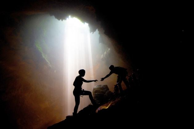 © Jeremy Piper. Light shines through the vertical limestone cave as a member from an expedition team is given a helping hand in the Jomblang Cave in Yogyakarta , Indonesia.
