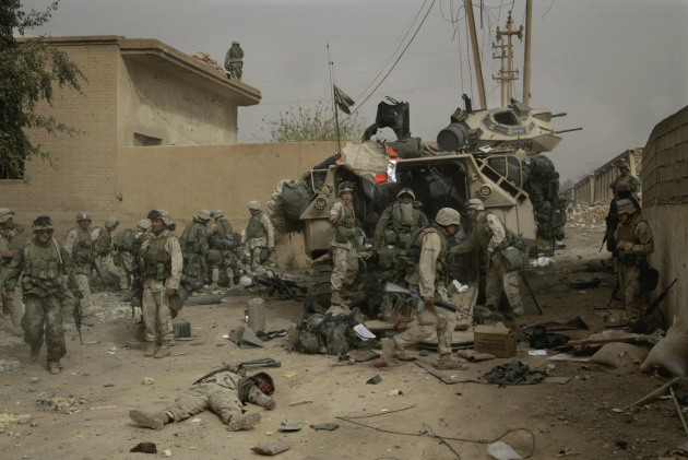 © Gary Knight. US Marines clean up their dead and wounded after a 130mm shell exploded in a direct hit on one of their armoured vehicles during an attack on Dyala Bridge during the invasion of Iraq. April 2003.