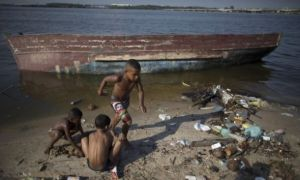 Boys play next to an abandoned boat, on the garbage-littered shore of Guanabara Bay in Rio. Photograph: Leo Correa/AP.