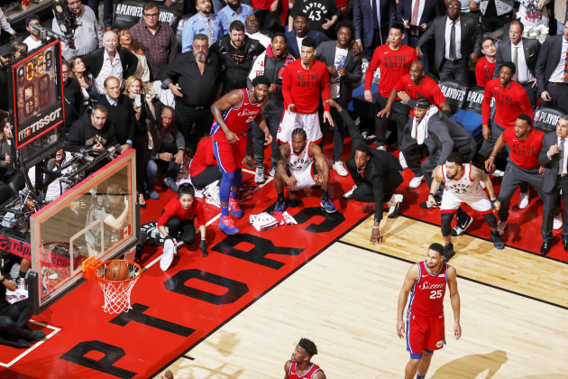 © Mark Blinch, for NBAE. Kawhi Leonard's Game 7 Buzzer Beater. Kawhi Leonard (squatting, center) of the Toronto Raptors watches his game-winning buzzer-beater shot go into the net, while playing against the Philadelphia 76ers in Game 7 of the Eastern Conference Semifinals of the 2019 National Basketball Association (NBA) Playoffs, at the Scotiabank Arena, Toronto, Canada, on 12 May 2019.
