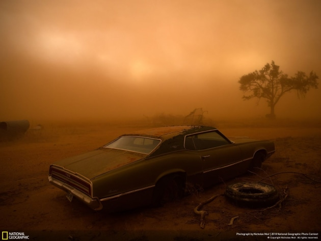 Photograph and caption by Nicholas Moir / 2018 National Geographic Photo Contest. A rusting Ford Thunderbird is blanketed by red dust from a supercell thunderstorm in Ralls, Texas. The dry, plowed fields of the Texas Panhandle made easy prey for the storm, which had winds over 90 miles an hour ripping up the topsoil and depositing it farther south. I was forecasting and positioning a team of videographers and photographers on a storm chase in Tornado Alley—this was our last day of a very successful chase, having witnessed 16 tornadoes over 10 days. The target area for a storm initiation was just south of Amarillo, Texas. Once the storm became a supercell, it moved southbound with outflow winds that were easily strong enough to tear up the topsoil and send it into the air.