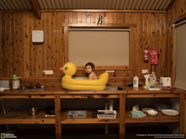Photograph and caption by Todd Kennedy / 2018 National Geographic Photo Contest. On a family holiday driving from Sydney to Uluru, we stopped at a roadside motel in the small rural township of Nyngan, on the edge of Australia's outback. The area is in the wheat belt, and it was unusually hot for that time of year—over a hundred degrees Fahrenheit and very dusty. Our daughter, Genie, is seen here enjoying a refreshing bath in a rubber ducky perched on the sink.
