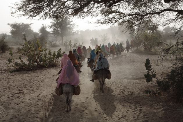 © Gary Knight. Displaced women ride from the Kutum market to the Fata Borno Camp for the displaced under escort by South African soldiers of the African Union in Sudan's troubled Darfur region, Jan. 19, 2007. The trek will take the women 15 kilometres (9 miles) through open territory. Women are frequently attacked and raped by government-allied Janjaweed militias when they venture out into open territory.