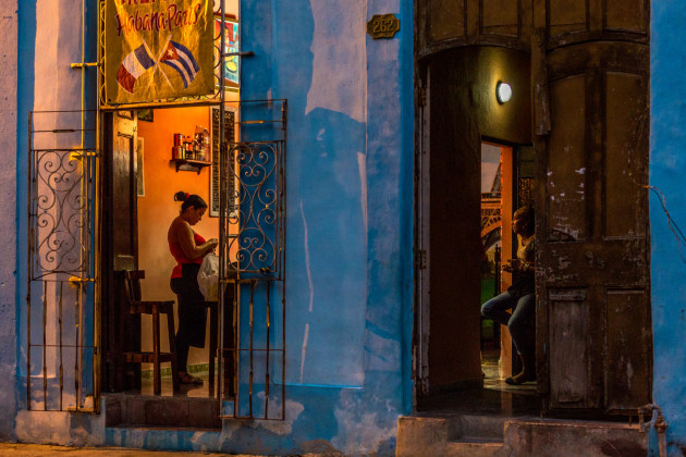 "© Sumit Dua, USA/UK. Winner – Dusk to Dawn. Havana, Cuba. ""Walking around the streets of Havana after sunset I came across this ordinary scene where two neighbours were chatting. The lighting and colours reminded me of the 'Old Master' paintings."""