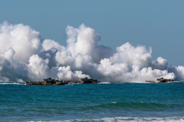 US Marine Corps amphibious assault vehicles give off tactical smoke as they approach Langham Beach. Credit: Defence