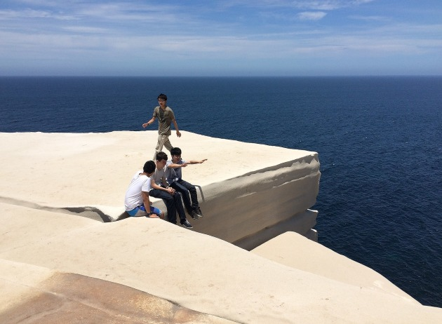 A group of visitors sitting on Wedding Cake Rock, pictured in December 2014, prior to the landmark's closure to the public.