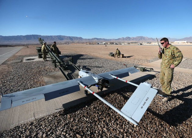 Corporal Scott McMahon, a Shadow Unmanned Aerial Vehicle maintainer and ground crew chief, communicates via radio with a Shadow launch commander during the pre-flight phase of a mission. Defence