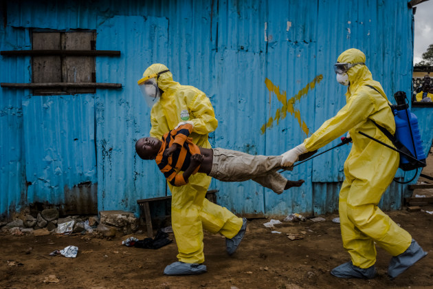 © Daniel Berehulak. James Dorbor, 8, suspected to have Ebola, is rushed in by medical staff wearing protective clothing into the JFK Ebola treatment centre on 5 September, 2014 in Monrovia, Liberia. He had been sick and showing symptoms for 3-4 days. Edward Dorbor, his father first took James to the S.O.S clinic, nearby for treatment, but being an ordinary hospital, medical staff were too afraid to treat the boy, as James was suffering with symptoms consistent with Ebola: extreme weakness, loss of appetite, toileting and vomiting. They referred him to the JFK Ebola treatment facility.