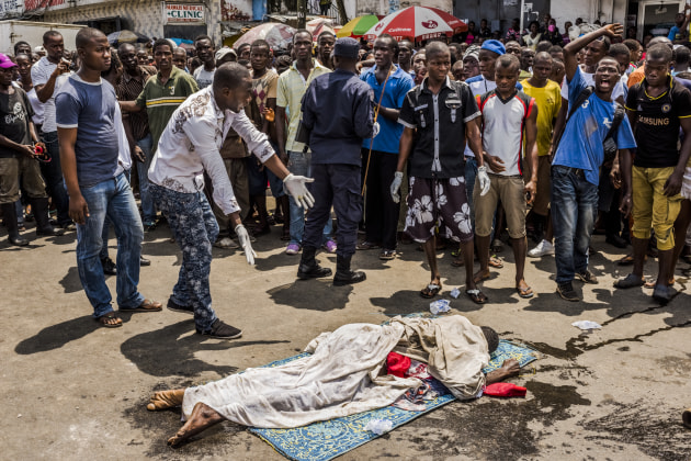 © Daniel Berehulak. Residents look on as a man lies dead in a busy street on September 15, 2014 in Monrovia, Liberia. According to locals, the man passed away three days ago. The family had been calling to have his body removed, but no burial team came to dispose of the body. People afraid that it was an Ebola death, wearing rubber gloves, dragged his body onto the busy street, stopping traffic, and drawing attention to have the body removed.