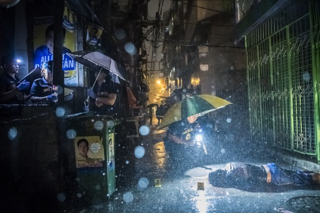 © Daniel Berehulak. Heavy rain pours as SOCO Police, Scene of the Crime Operatives, investigate inside an alley where victim, Romeo Joel Torres Fontanilla, 37, was killed by  two unidentified gunmen riding motorcycles early Tuesday morning on October 11, 2016 in Manila, Philippines. Shot for The  New York Times.