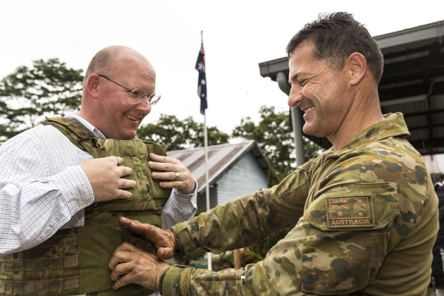 Australian Army soldier Corporal James Boulton (right) helps his civilian employer, Mr Robert Warburton, try on body armour. The light weight of XTEK's SAPI plates was a major selling point.