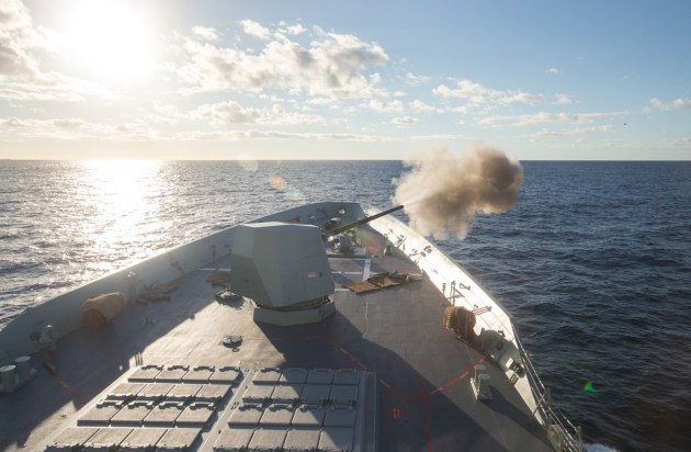 The Mark 45 Mod 6 5-inch gun of HMAS Hobart engages a towed surface target during weapon trials. 