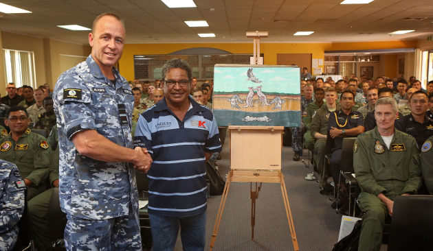 AVM Steven Roberton is officially presented with the Exercise PITCH BLACK 18 artwork from Mr Joe Raymond of the Larrakia people, surrounded by International multi-nation Air Force representatives. Defence