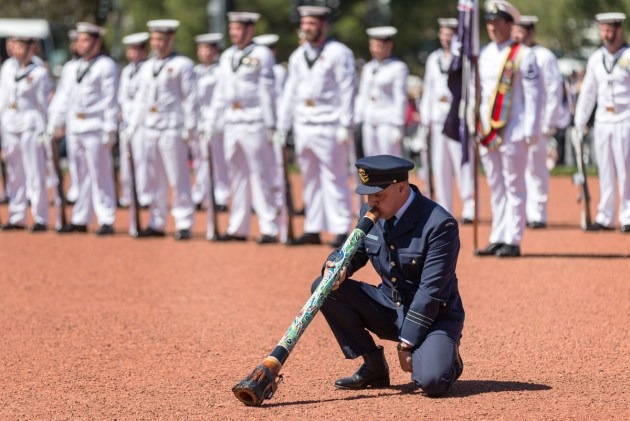 RAAF officer Wing Commander Jonathan Lilley plays the didgeridoo during the Remembrance Day Ceremony at the Australian War Memorial, Canberra. Defence