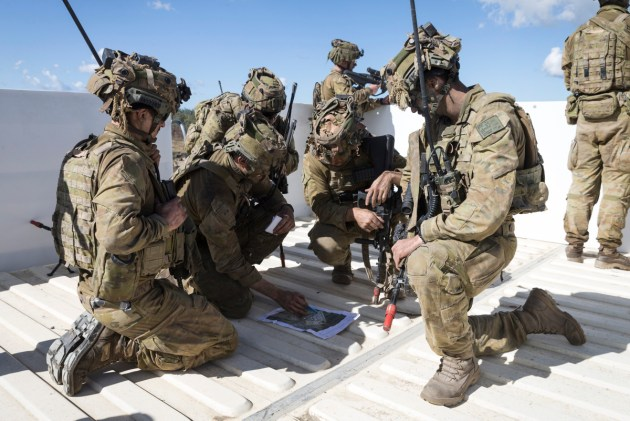 Soldiers from the Australian Army's 7th Battalion, Royal Australian Regiment plan a path through the town of Raspberry Creek during Exercise Talisman Sabre. (Defence)