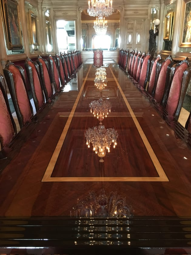 This 32 foot dining table with accompanying 26 chairs was a two month long commission. The table was made in eight foot sections from curly mahogany with sycamore banding .