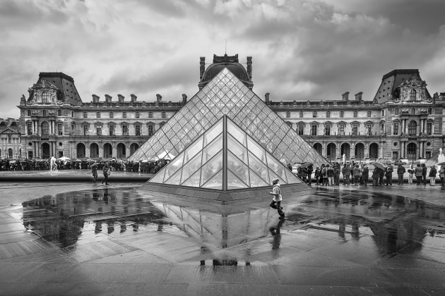 "© Katy Gomez Catalina, Spain. Overall winner- Travel Photographer of the Year 2019. Paris, France. ""It was raining and people formed a perfect row to enter the Louvre Museum.The only dynamic note of the scene was a boy who ran across."""