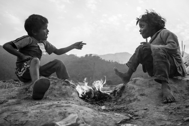 Raju and Sajila enjoy the warmth of their little campfire as they dream of a world beyond their surroundings. They are children of itinerant families who come from the Tarai plains and travel in the central valleys of Nepal. They have no schooling but are remarkably brave and resourceful. Chhorepatan, Nepal. © Didier Mayhew.