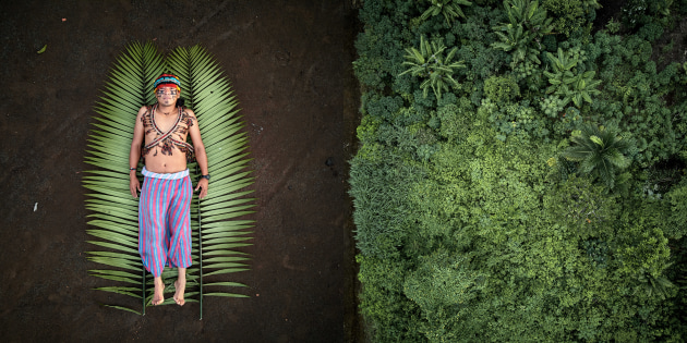 © Pablo Albarenga, Uruguay, Photographer of the Year, Professional, Creative, 2020 Sony World Photography Awards. From the series, Seeds of Resistance. José is one of the leaders of the Achuar indigenous people in the Sharamentsa community. He defends his rainforest by generating projects in collaboration with external organisations. One of them aims to create an indigenous group to monitor their territory from the ground and also by using aerial technology such as drones. Left: José lying down in his yard over a banana leaf, dressed in traditional Achuar clothing. Right: The Achuar rainforest at the back of José's house. Sharamentsa, Pastaza, Ecuador.