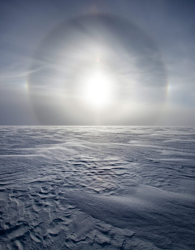 A sun dog on the Greenland ice sheet. Sun dogs are optical halos that are visible around the sun from the ice crystals in the air, 2010. © Sebastian Copeland.