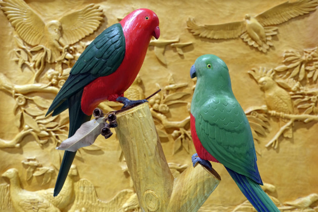 Kevin Gillis's King Parrots carved from jacaranda and jelutong stand before 'Australian Bird Collection', a wall-mounted relief carving in Huon pine made by three members of the Sydney Woodcarving Group for a raffle a few years ago.